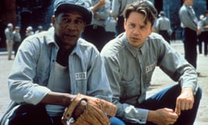 Morgan Freeman and Tim Robbins in prisoners uniforms crouched next to each other