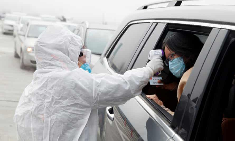 A medical worker checks the body temperature of a car passenger in China's Hunan province. Shares have fallen on fears about the spread of coronavirus.