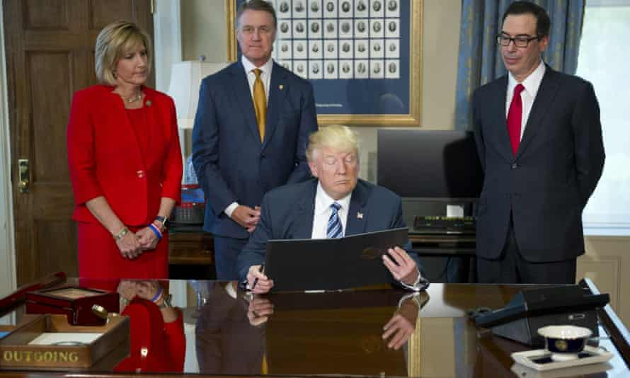 Donald Trump looks over the document prior to signing the first of three executive orders concerning financial services at the Department of the Treasury in Washington DC on 21 April 2017.