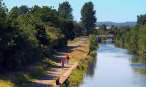 Cyclists ride alongside the Forth and Clyde canal at Clydebank.