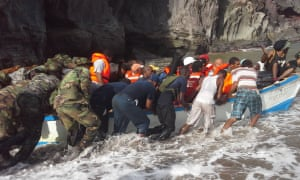 Rescuers assist villagers in a boat during evacuation efforts in Petite Savanne, Dominica.