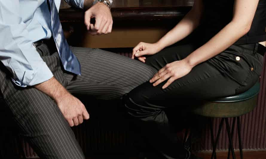 Low section view of couple flirting at bar