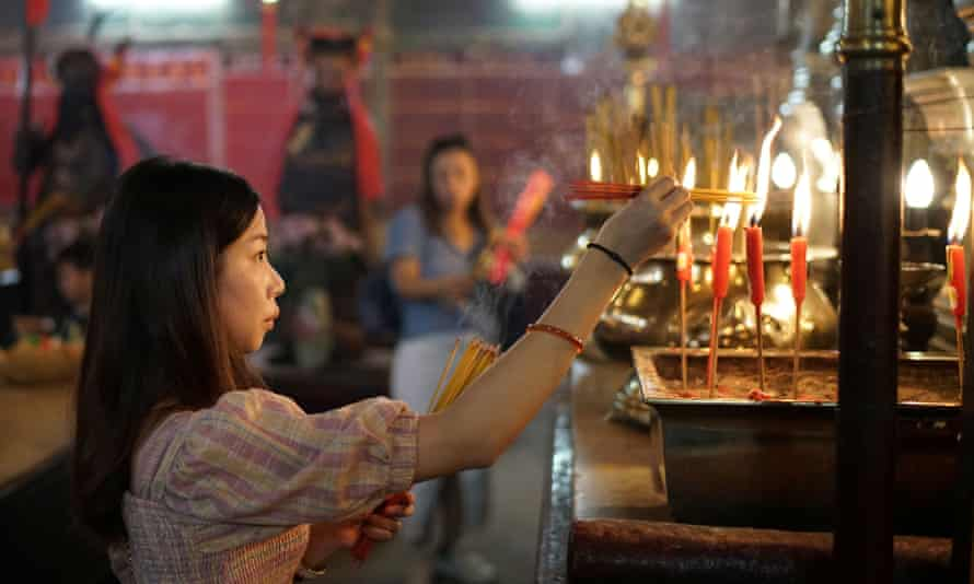 A woman burns incenses as she prays at Man Mo Temple in Hong Kong