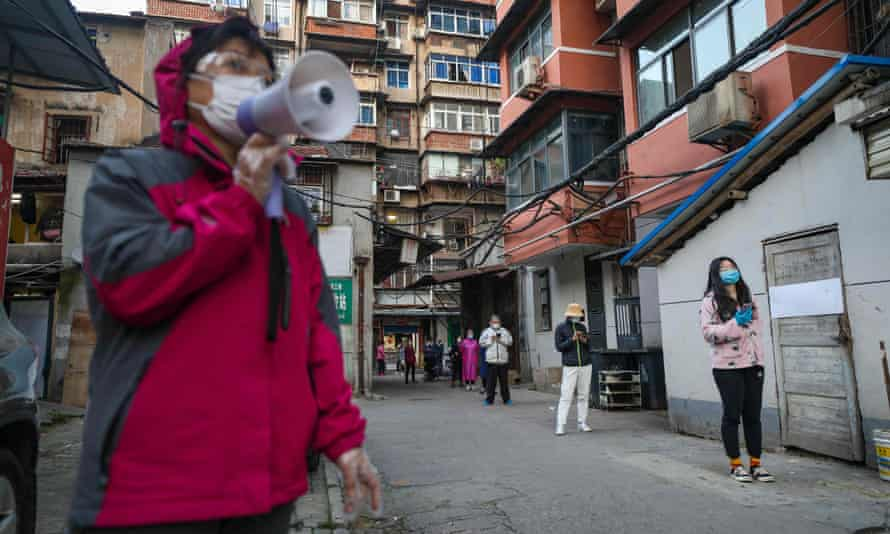 Residents line up to receive pork delivered to their quarantined compound in Wuhan, Hubei province.