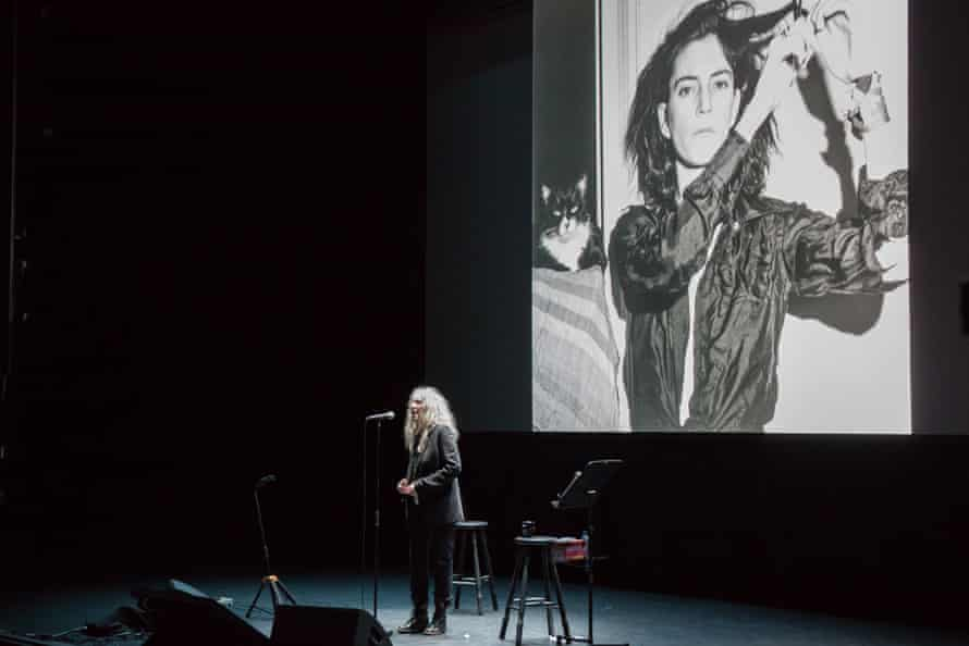 Patti Smith backed by a photograph taken by former lover and collaborator Robert Mapplethorpe.