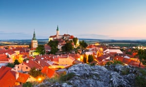 At dusk and with street lights on, an aerial view of historic old town of Mikulov in Moravia, Czech Republic. This view shows the castle of Mikulov.
