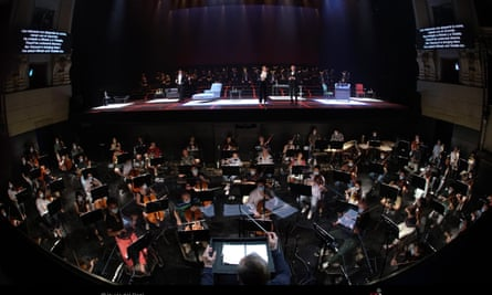 The Teatro Real orchestra in face masks, with the conductor separated by screens.
