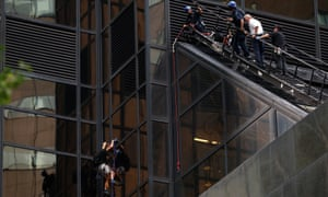 Officers from the NYPD watch as a man climbs the outside of Trump Tower in New York.