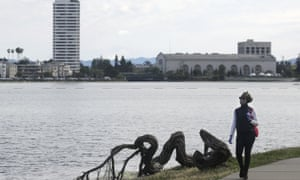 A woman wears a face mask while walking at Lake Merritt. Nooses were found hanging in trees in the area.