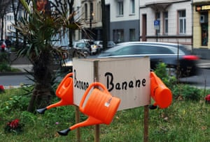 Cologne-Suedstadt, Germany. Watering cans hang on a sign near banana trees