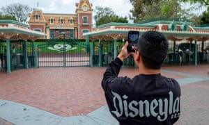 A man takes a photo outside the gates of the closed Disneyland Park in California.