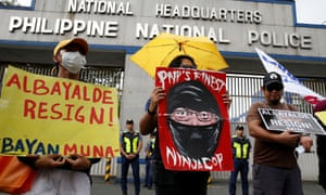 Protesters display placards during a rally outside the Philippine national police headquarters to demand the resignation of retiring police chief over drugs allegations.