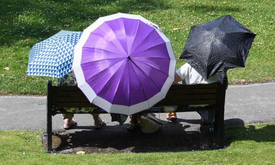 People in the sun with umbrellas