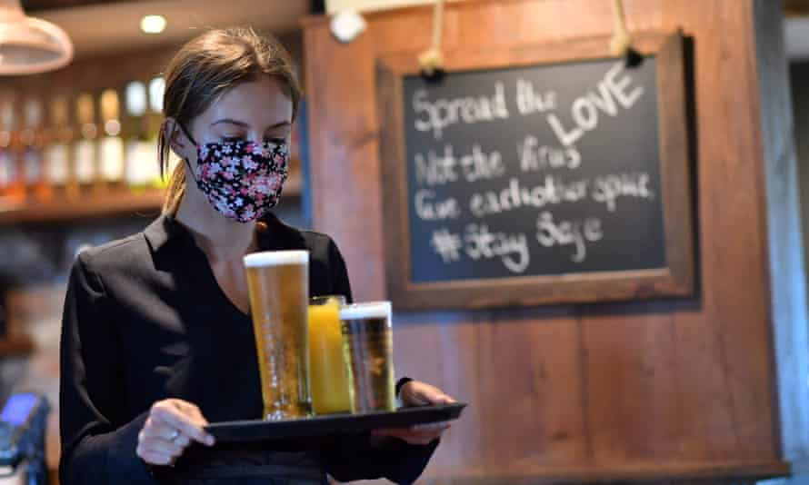 A woman delivers drinks in a pub