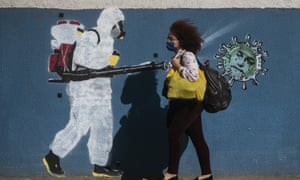 A woman wearing a mask walks past a wall with a graffiti depicting a cleaner in protective gear spraying viruses with the face of President Jair Bolsonaro in Rio de Janeiro.
