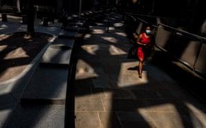 A woman walks under the Gherkin skyscraper, July 2020