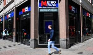 Man walks past a Metro Bank branch