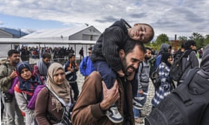 Migrants and refugees stand in line as they wait to board a train at the registration camp after crossing the Macedonian-Greek border near Gevgelija on September 28, 2015.