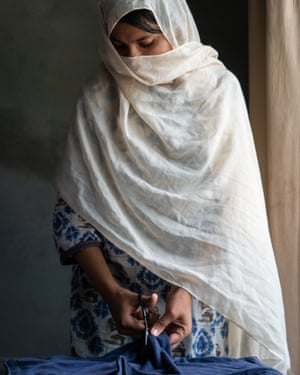 Saba, 18, cuts a cloth to use during her period in Islamabad, Pakistan