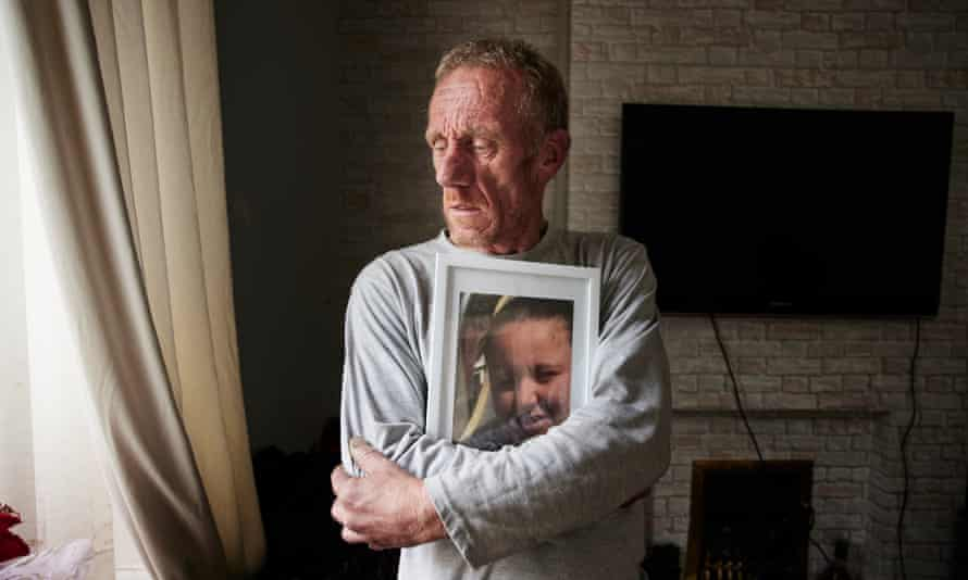 Kelsey Devlin's father, Sean Devlin, holding a framed photograph of her in Burnley