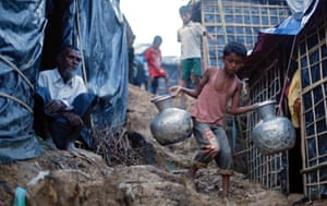 A Rohingya refugee boy walks down a hill with metal pitchers at a makeshift camp in Cox's Bazar, Bangladesh