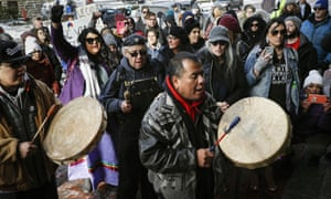A protester leads a Native American prayer with a traditional drum outside the Catholic diocese of Covington on Tuesday in Covington, Kentucky.