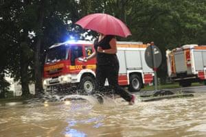 A woman walks past fire trucks at a flooded street in Düsseldorf, Germany