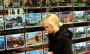A young woman walking past estate agent window