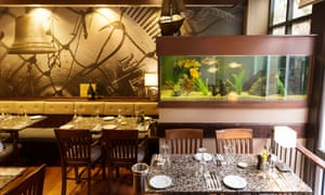 A set table and a fish tank in the dining room of  Fishers in the City restaurant