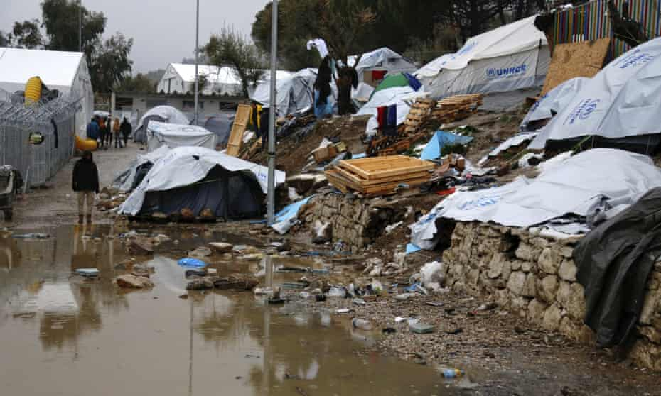 A refugee stands next to a pool of mud at Moria refugee camp in Lesbos