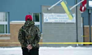 A man holds a rosary outside the La Loche community school.