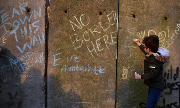 A young protester writes slogans on a mock border wall and customs checkpoint in Louth, Ireland, in January
