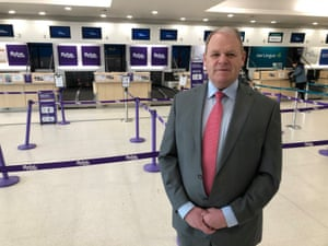 Chief executive of Belfast Airport, Brian Ambrose, speaking to the media in front of the empty Flybe check-in desks this morning