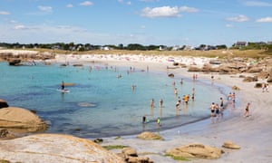 Sunbathers and swimmers at a Brittany beach.