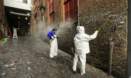 To workers try to clean layers of gum from Seattle's famous gum wall at Pike Place Market