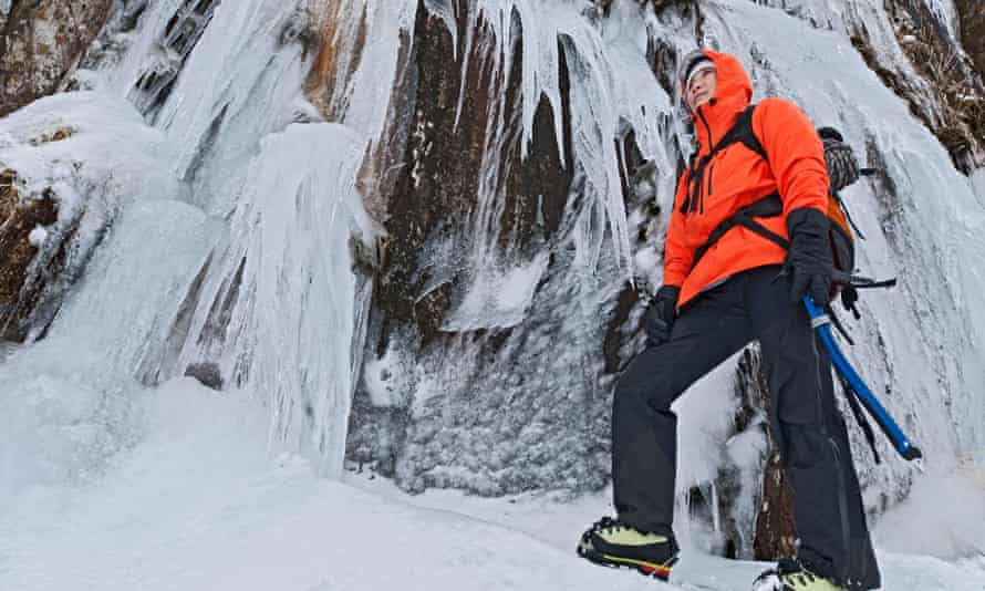 Female climber in front of frozen waterfall, Snowdonia