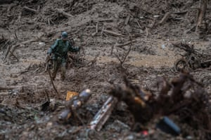 A soldier wades through mud as he looks for bodies at the site of a landslide in Tsunagi
