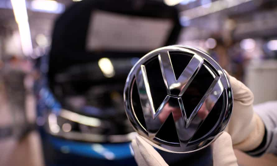 An employee holds a Volkswagen logo in a production line at the VW plant in Wolfsburg, Germany