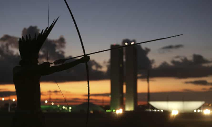 A Pataxo indegenous man notches his arrow, backdropped by the National Congress, in Brasília.