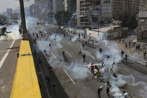 Demonstrators throw teargas canisters back at riot police during a protest in Caracas