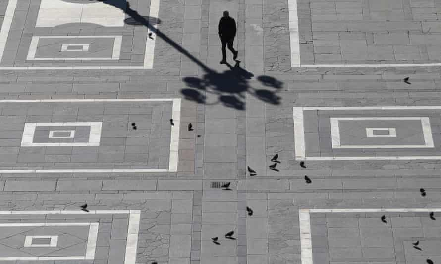 A man walks across the normally crowded Duomo square in central Milan on Sunday