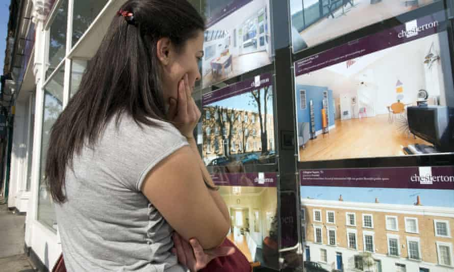 Young first time buyer looking at houses for sale in estate agent window in Islington, London