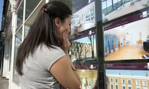 A young woman looking at houses in an estate agent's window.