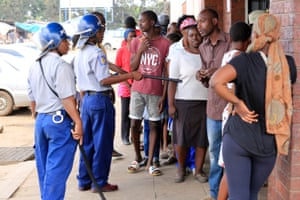 A police officer orders shoppers to maintain a social distance as they wait to buy essentials outside of a shop in Harare, Zimbabwe, on Monday