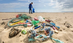 Man picking up plastic pollution collected on beach in north-east England