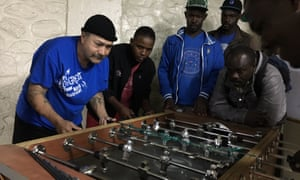 A deported Mexican migrant plays table football with Haitians at a Tijuana shelter.