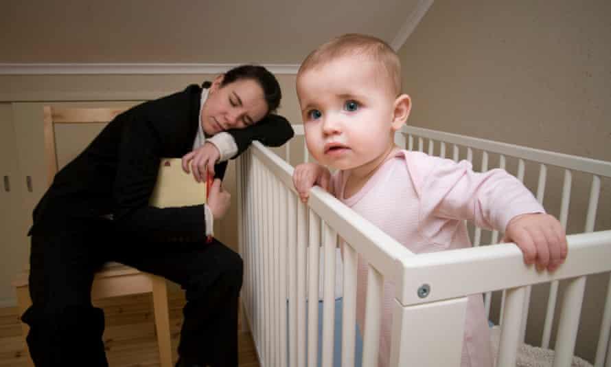 Mother asleep beside cot with baby awake