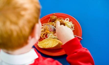 A boy eating a school dinner