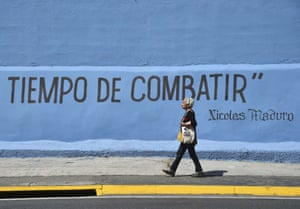 """A woman passes by a graffiti with a partial phrase attributed to Venezuelan President Nicolas Maduro reading """"Time to Fight"""", in Caracas"""
