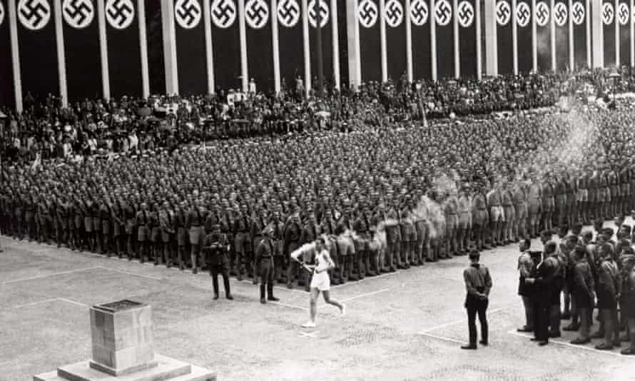 The Olympic torch is carried into the stadium in Berlin on 1 August 1936.